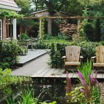 Tuin met een vlonder over de vijver. Verschillende hagen en beplanting.