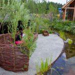 Tuin met hoogte verschillen, regenwatervijver en verschillende beplanting.